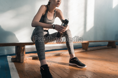 partial view of sporty woman sitting