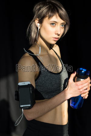 portrait of sporty woman listening music