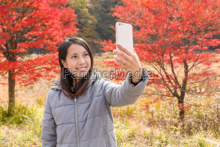 woman taking selfie with maple tree