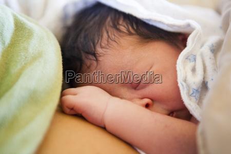 ein neugeborenes baby schlaeft auf der