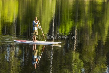 ein mann paddleboarding auf long pond