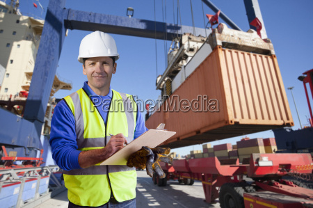 worker supervising loading of containers at