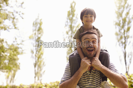 father giving son ride on shoulders