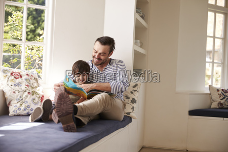 father and son reading story at