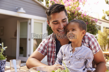 father and son eating outdoor meal