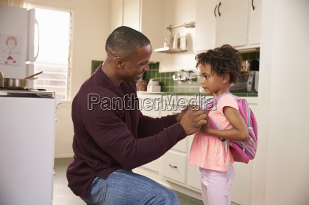 father helps daughter with backpack as