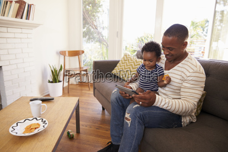 father and son sitting on sofa