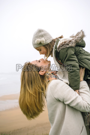 woman lifting up and kissing daughter