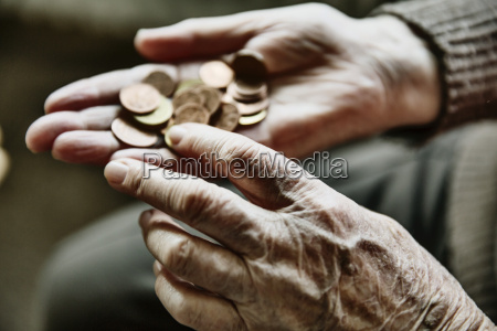 senior womans hands with coins