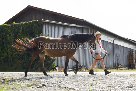 girl walking with horse on farm