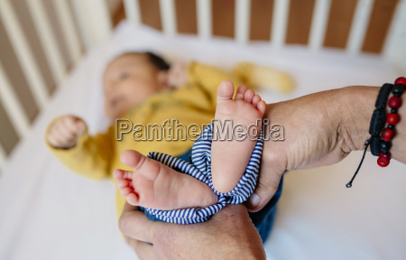grandmothers hands holding babys feet lying