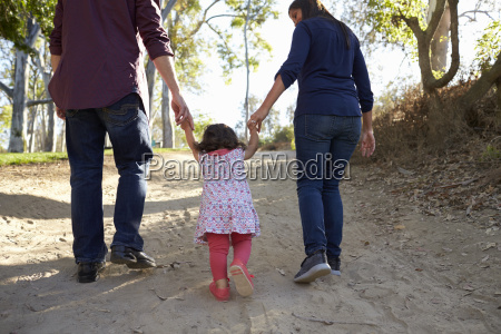 parents and young daughter walk hand