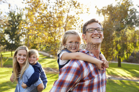 parents carry kids piggyback in park