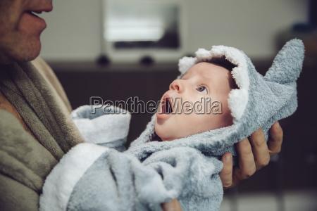 father holding baby wearing shark bathrobe