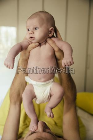 newborn baby in diapers being held