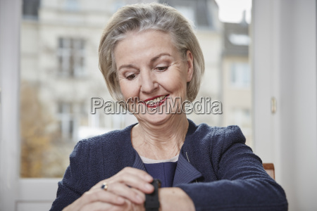 smiling senior woman looking at watch