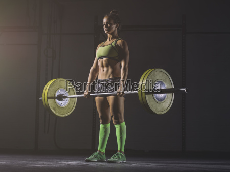 young woman lifting barbell