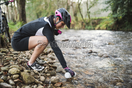 female mountain biker filling a bottle