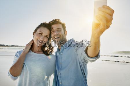 portrait of happy couple taking selfie