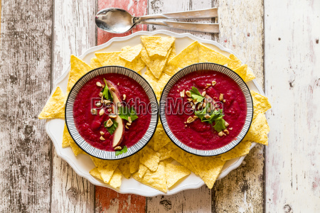 two bowls of beetroot soup garnished