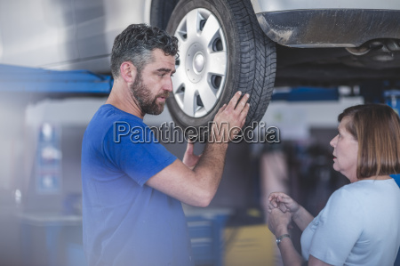 mechanic in workshop with customer