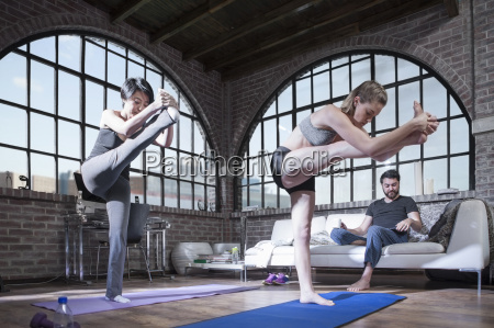 two women doing yoga exercise in