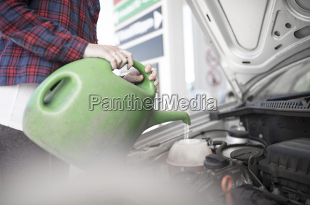 woman filling up car with water