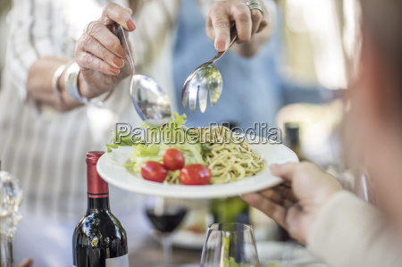 dishing up salad and spaghetti for