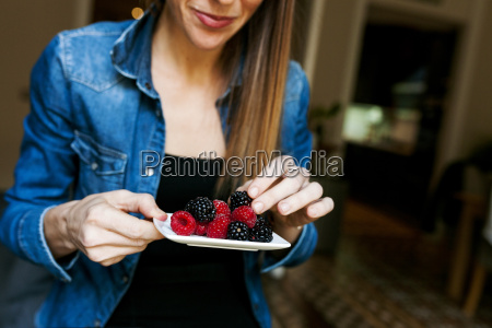 young woman eating berries
