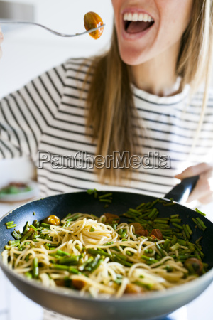 young woman holding pan with vegan