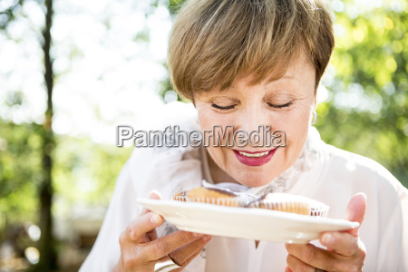 senior woman holding plate of muffins