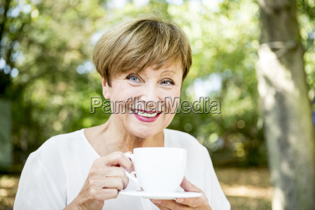 portrait of smiling senior woman drinking