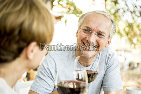 smiling senior couple clinking red wine
