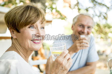 smiling senior woman drinking glass of