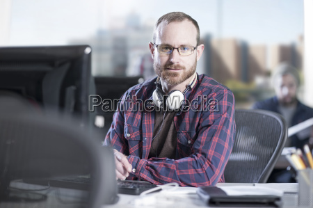 portrait of confident man at desk