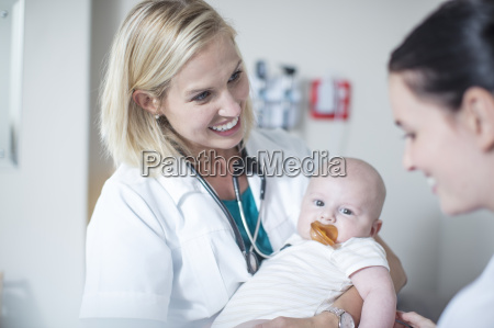 female pedeatrician holding baby at examination