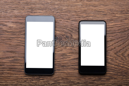two mobile phones on wooden desk