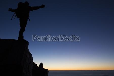 silhouette des wanderers auf bergkamm morgendaemmerung
