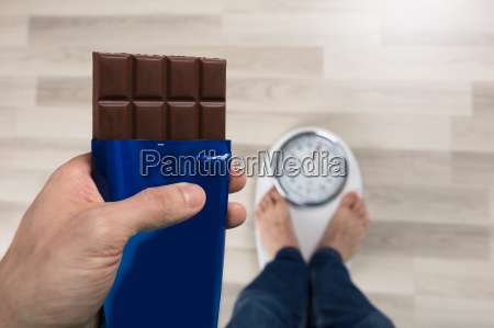 person holding chocolate measuring weight