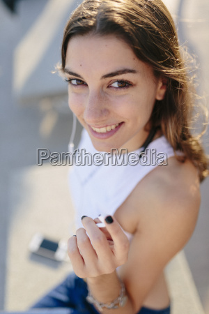 portait of smiling young woman listening