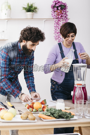 couple preparing smoothies with fresh fruits