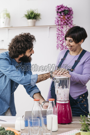 happy couple preparing smoothies with fresh