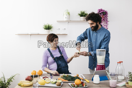 smiling ccouple preparing healthy smoothies with