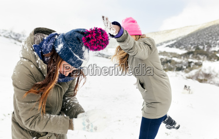 friens having a snowball fight in