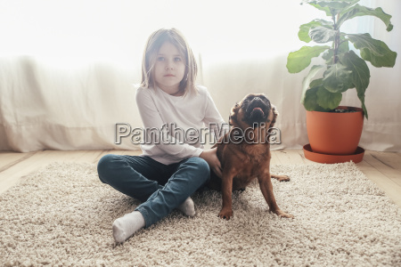 little girl sitting with her dog
