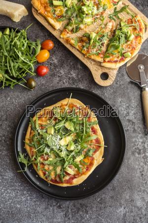 vegetarian pizza with avocado rocket tomatoes