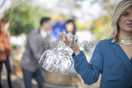 young woman holding wine glasses outdoors