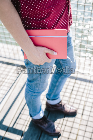 cloe up of man holding notebook