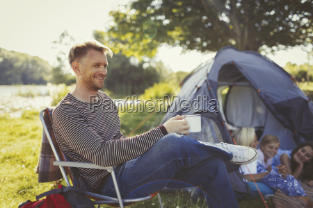 smiling father drinking coffee outside tent