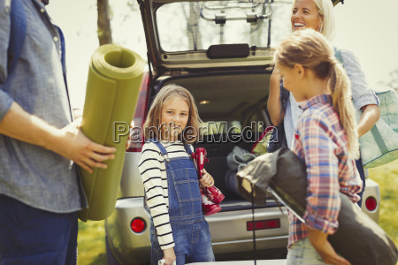 portrait smiling girl with family unloading